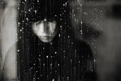 Mujer mirando ventana lluvia con melancolia.